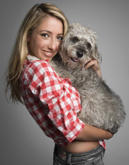 Studio portrait of cute girl wearing red and white checked shirt holding her dog