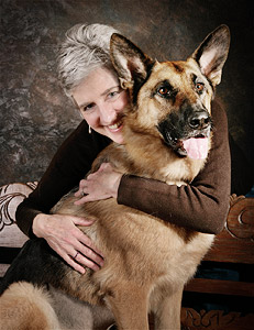 Studio portrait of older woman hugging German Shepherd dog on brown background
