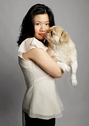 Studio portrait of woman holding Pekinese dog on gray background